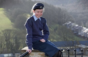 Air Cadet Mya Larder pictured wearing her uniform sitting on a wall smiling directly at the camera.