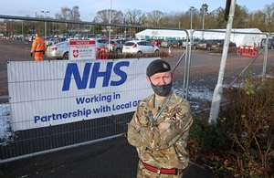 Man in British Army uniform standing with his arms crossed in front of a sign that reads NHS.