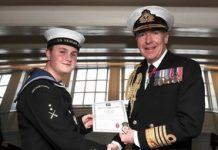 Sea cadet John Challenger being awarded a British Empire Medal (BEM) dressed in full service uniform.