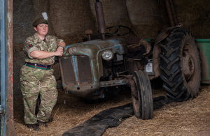 Reservist Tracy Llewellyn standing next to a tractor dressed in full service uniform.